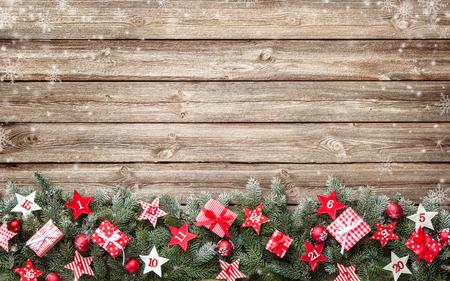 アドベント カレンダー星と古い木製ボード上のギフト ボックスとモミの木の枝