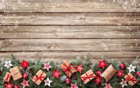 Dennenboom takken met adventskalender sterren en geschenkdozen op oude houten plank Stockfoto