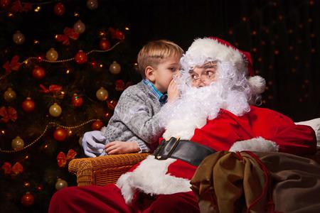 Kerstman en een kleine jongen. Jongen vertelt wensen in de voorkant van de kerstboom