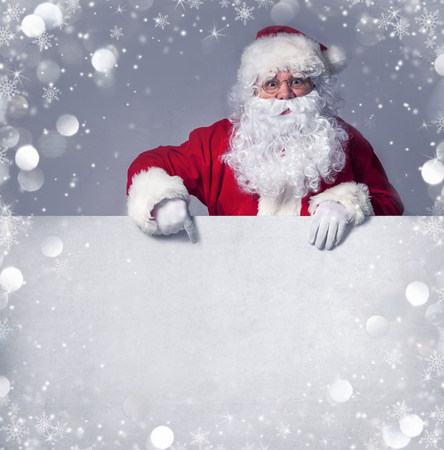 Santa Claus pointing in blank sign photo