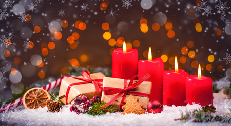 Advent decoration with four burning candles and gift boxes. Christmas background