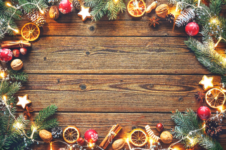 lighting background: Christmas decoration with fir tree, oranges, cones, nuts, spices, cookies and lights on a wooden table