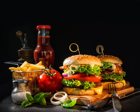 Delicious hamburgers with french fries and ketchup on dark background