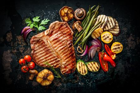 焼き野菜と暗い背景に調味料牛肉の t ボーン ステーキ 写真素材