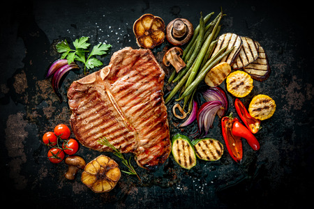 Beef T-bone steak met gegrilde groenten en kruiden op een donkere achtergrond