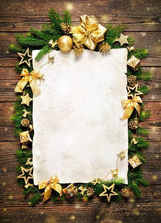 Old paper bordering with christmas decoration on wooden background Stock Photo