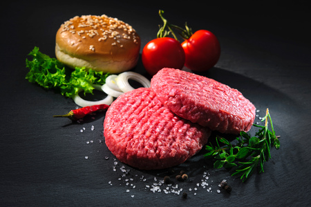 自家製ハンバーグ。生牛肉のパテ、暗いスレート板上ハンバーガーの他の成分とゴマのパン