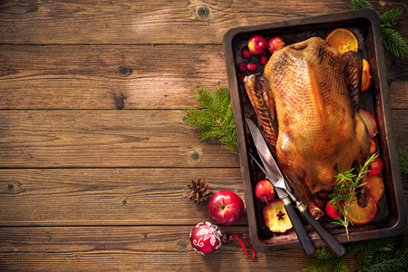 Roast duck with apples and oranges on baking tray. Cooking at Christmas time Banco de Imagens - 66933022