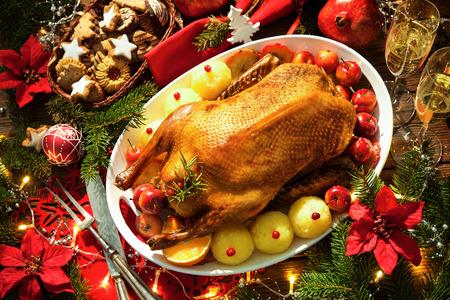 arandanos rojos: pato asado de Navidad sirvió en una mesa de fiesta