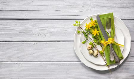 水仙とカトラリー イースター テーブルの設定。休日の背景