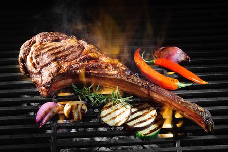 Tomahawk rib biefstuk op hete zwarte grill met vlammen