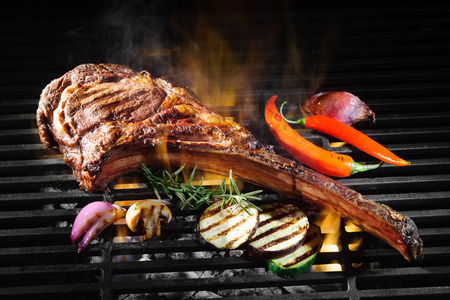 Tomahawk Rippe Beefsteak auf heißen schwarzen Grill mit Flammen Standard-Bild - 70551461
