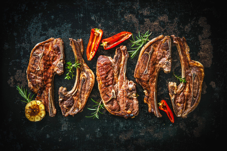 cutlets: Roasted lamb meat with vegetables on dark background Stock Photo