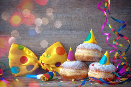 Carnaval gepoederde suiker opgeheven donuts met papier streamers en feeststropdas Stockfoto