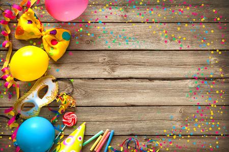 木製の背景のパーティー アイテムがカラフルな誕生日やカーニバルのフレーム