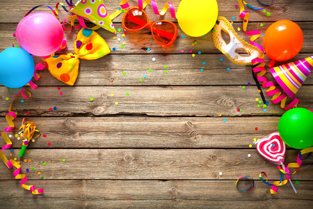 Colorful birthday or carnival frame with party items on wooden background Фото со стока