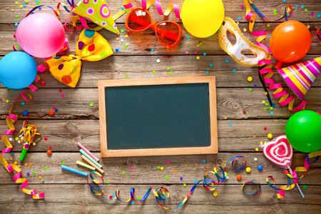 marco cumpleaños: Marco de cumpleaños o el Carnaval colorido con artículos de fiesta en fondo de madera Foto de archivo