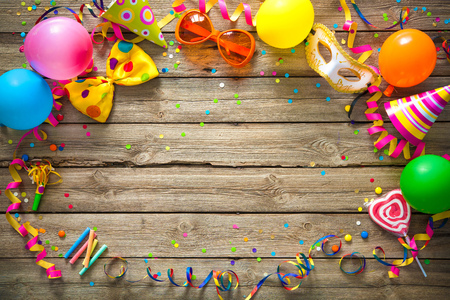 Colorful birthday or carnival frame with party items on wooden background Foto de archivo