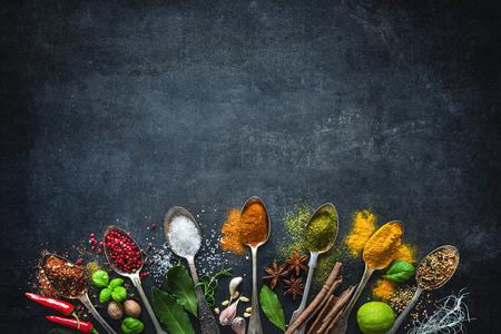 Verschillende kruiden en specerijen op zwarte stenen plaat