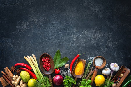 Various herbs and spices on black stone plate Фото со стока