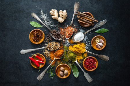 Various herbs and spices on black stone plate Stock Photo