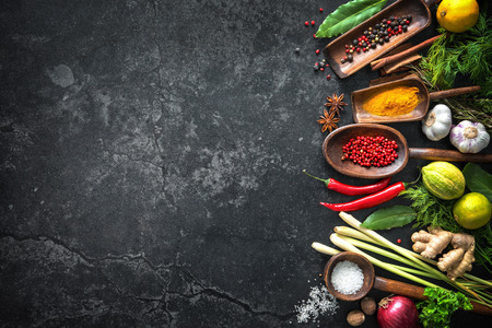 multiple: Various herbs and spices on black stone plate Stock Photo