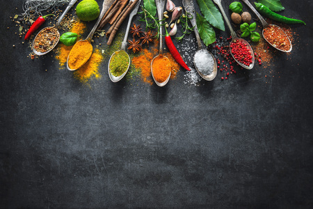Various herbs and spices on black stone plate Stockfoto