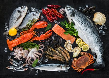 Pesce e frutti di mare arrangiamento fresco su sfondo nero di pietra Archivio Fotografico - 73220477