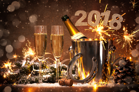 New Years Eve celebration background with pair of flutes and bottle of champagne in  bucket  and a horseshoe as lucky charm Фото со стока - 73220478