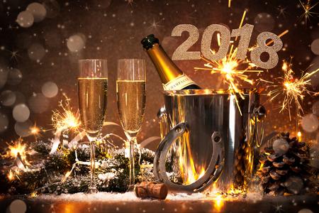 Nochevieja fondo de la celebración con pares de flautas y botella de champán en un cubo y una herradura como amuleto de la suerte Foto de archivo - 73220478