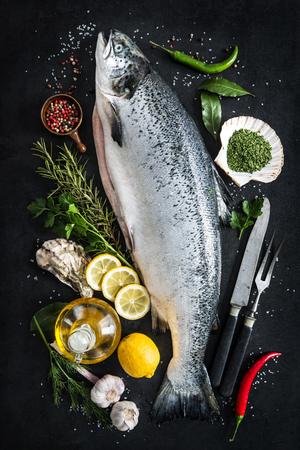 黒い石のテーブルに調味料と新鮮なサーモン魚