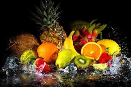 Frutas en el fondo negro con salpicaduras de agua