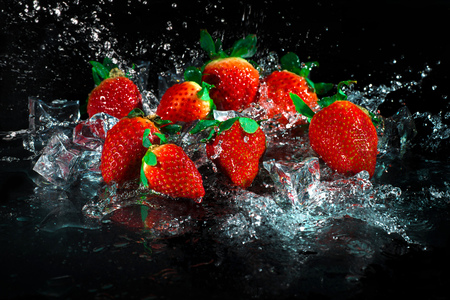 water wave: Strawberries in water splash on black background