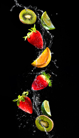 Frische Früchte in Wasser Splash fallen auf schwarzem Hintergrund isoliert Standard-Bild - 73220484