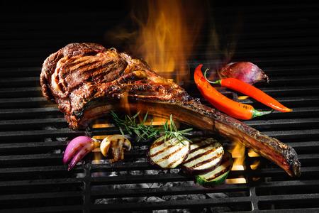 Tomahawk 갈비 쇠고기 스테이크와 뜨거운 블랙 그릴 화 염에