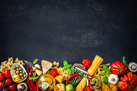 comida italiana: Cocina italiana. Verduras, aceite, especias y pastas en fondo oscuro Foto de archivo