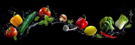 水のしぶきと黒の背景の野菜