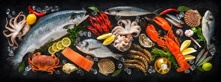 Verse vis en zeevruchten arrangement op zwarte steen achtergrond Stockfoto