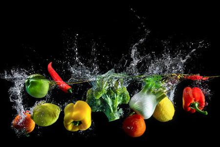 Groenten plons in water op zwarte achtergrond Stockfoto