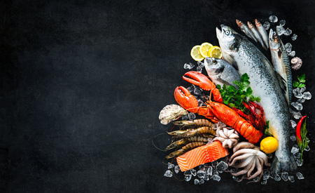 Fresh fish and seafood arrangement on black stone table