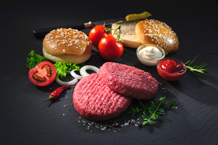 uncooked: Homemade hamburger. Raw beef patties, sesame buns with other ingredients for hamburgers on dark slate plate