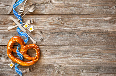 traditional: Bavarian pretzel with ribbon and silverware on wooden board. Background for Oktoberfest