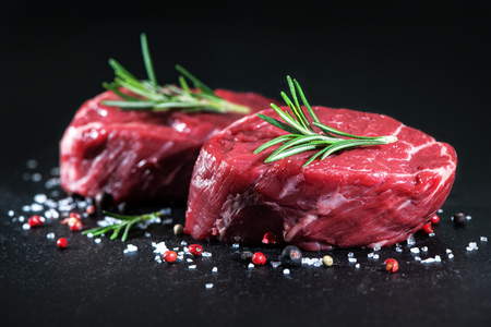 Raw beef fillet steaks with spices on on dark background