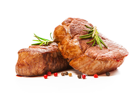 Grilled beef fillet steaks with spices isolated on white background