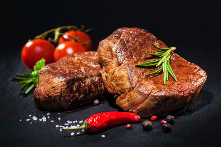 Bistecche di filetto di manzo alla griglia con spezie su sfondo scuro Archivio Fotografico - 74154747