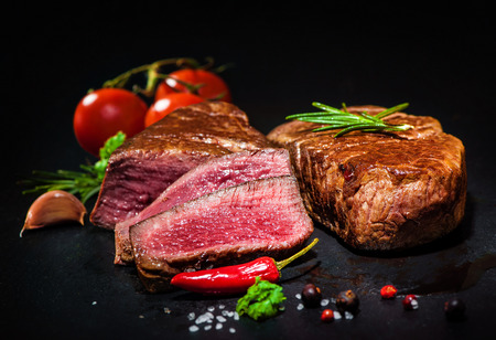 grilled beef fillet steaks with spices on dark background Stock Photo