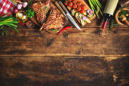 Gegrilde T-bone steaks met verse kruiden, groenten en wijnfles op rustieke houten plank Stockfoto - 76548384
