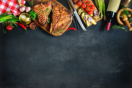 Biftecks ??T-bone grillé avec herbes fraîches, légumes et bouteille de vin Banque d'images - 76548389