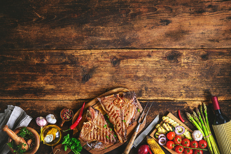 新鮮なハーブ、野菜や素朴な木の板にワインのボトルとグリルの t ボーン ステーキ 写真素材