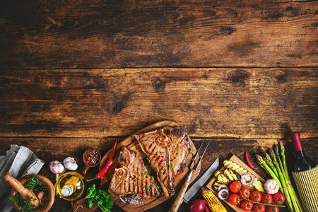 Biftecks ??T-bone grillés avec des herbes fraîches, des légumes et une bouteille de vin sur un plateau de bois rustique Banque d'images